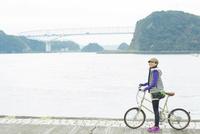 自転車を押し海辺に立つ女性