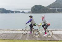 自転車で海辺を走る2人の女性