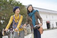 自転車を押して佇む2人の女性