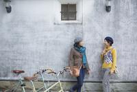 壁にもたれて会話をする2人の女性