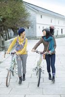 自転車を押して歩く2人の女性
