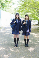 新緑の並木道に立つ2人の女子高生