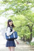 新緑の並木道で振り向く女子高生