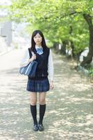 新緑の並木道に立つ女子高生