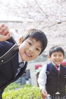桜の木の前で笑う兄弟