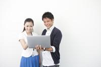ノートパソコンを見る男女