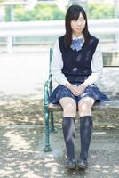 ベンチに座る日本人の女子高生