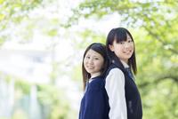 背中合わせに立つ2人の日本人女子高生
