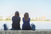 防波堤に座る2人の日本人女子高生