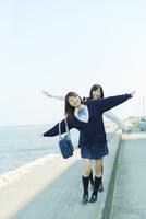 防波堤を歩く2人の日本人女子高生