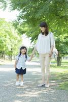 母親と手を繋いで立つ幼稚園児
