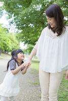 母親と手を繋ぐ女の子
