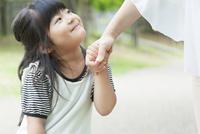 母親と手を繋いで笑う女の子