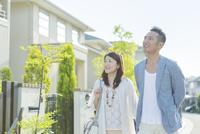 住宅の前に立つに日本人カップル