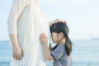 妊婦の母のお腹に顔をつける娘 10272005132| 写真素材・ストックフォト・画像・イラスト素材|アマナイメージズ