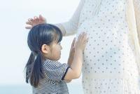 妊婦の母のお腹を触る娘
