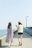 防波堤を歩く2人の女性
