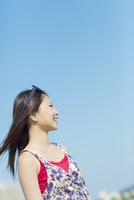 青空の下で髪をなびかせ微笑む女性