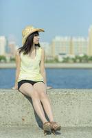 防波堤に座る日本人女性