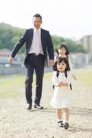 土手を歩く日本人の親子