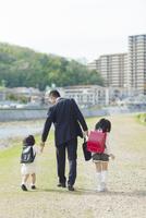 手を繋いで歩く父と娘