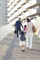 手を繋いで歩く4人家族