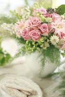 ピンクのバラの花アレンジと皿に乗せた菓子