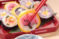 箸でつまんだ太巻き寿司