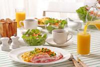 コップに注ぐオレンジジュースと朝食