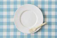 水色のチェックの布と白い皿とカトラリー