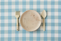 水色のチェックの布と木の皿とカトラリー
