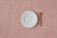 白い皿とピンクの布と木のカトラリー