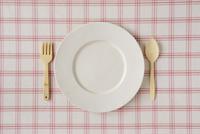 ピンクのチェックの布と白い皿と木のカトラリー