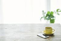 コーヒーカップとテーブルとカーテンとスマートフォン 10331002474| 写真素材・ストックフォト・画像・イラスト素材|アマナイメージズ