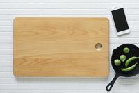 キッチンに置かれたカッティングボードと野菜とスキレットとスマートフォン 10331002558| 写真素材・ストックフォト・画像・イラスト素材|アマナイメージズ