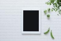 キッチンに置かれた白いタイルと野菜と観葉植物とタブレットPC 10331002576| 写真素材・ストックフォト・画像・イラスト素材|アマナイメージズ