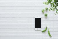 キッチンに置かれた白いタイルと野菜と観葉植物とスマートフォン 10331002577| 写真素材・ストックフォト・画像・イラスト素材|アマナイメージズ
