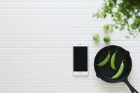 キッチンに置かれた白いタイルと野菜と観葉植物とスマートフォンとスキレット 10331002580| 写真素材・ストックフォト・画像・イラスト素材|アマナイメージズ