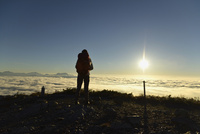 雲海と日の出を見る登山者