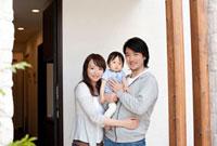 赤ちゃんを抱き玄関に立つ家族
