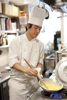 レストラン厨房でシェフがフライパンを振り料理を作る