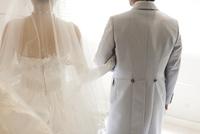 結婚式で腕を組み歩く新郎新婦の後ろ姿