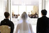 教会結婚式に向かう花嫁と両親の後ろ姿