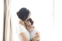 お母さんに甘えて抱っこされごきげんに笑う赤ちゃん