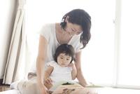 リビングで赤ちゃんを抱っこしながら絵本を読んであげる笑顔のお母さん