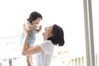 お母さんに抱っこされ高く持ち上げられて笑って喜ぶ赤ちゃん