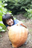 畑で見つけた大きなかぼちゃを持つ笑顔の男の子