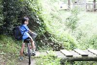 自転車に乗って森の中で振り返る笑顔の男の子