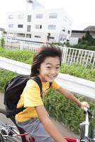 道路を自転車に乗って走る笑顔の男の子