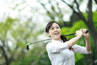 ゴルフをしている中年の女性